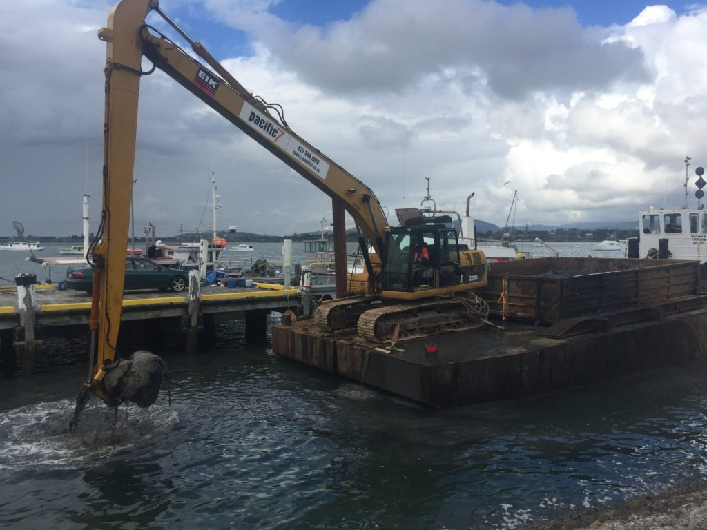 Dredging yellow digger is on a workboat